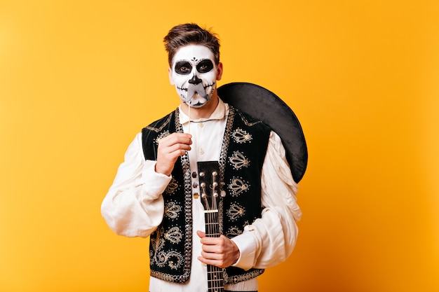 Un mec maquillé pour halloween et sombrero derrière le dos s'amuse et pose avec de fausses moustaches.