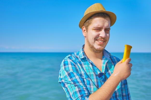Un mec met une crème solaire sur le visage. un homme au bord de la mer, le visage couvert de crème solaire.