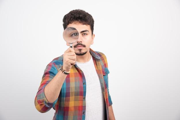 Un mec met une loupe à ses yeux pour voir plus grand.