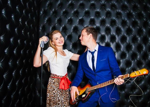 Un mec mignon et une fille chantant dans le micro en studio