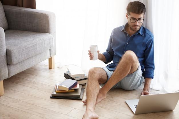 Un mec à la mode attrayant aime passer du temps à la maison, aime l'atmosphère domestique