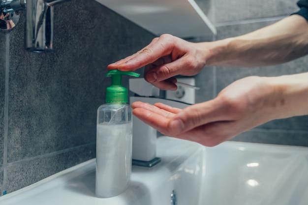 Un mec moderne se lave les mains dans la salle de bain