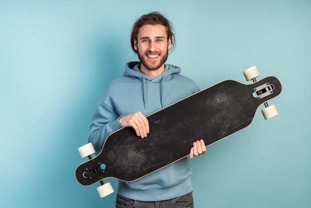 Mec moderne tenant un patin dans ses mains. jeune hipster.