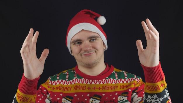Un mec montre quelque chose de grand avec un chandail du nouvel an