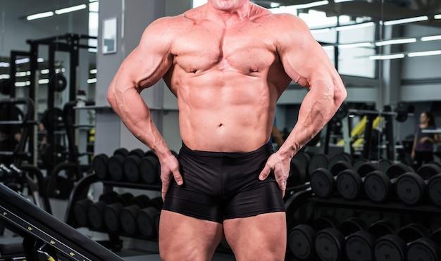 Mec musclé bodybuilder debout sur une salle de sport et posant le muscle triceps