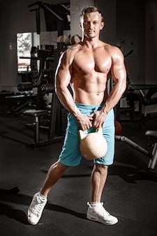 Mec musclé bodybuilder faire des exercices avec poids dans la salle de gym