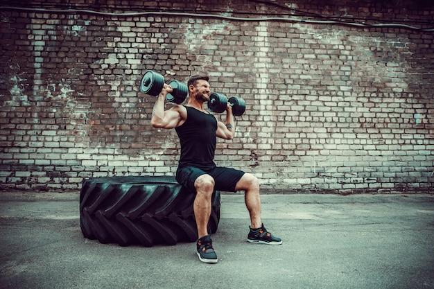 Mec musclé, faire des exercices avec haltère contre un mur de briques