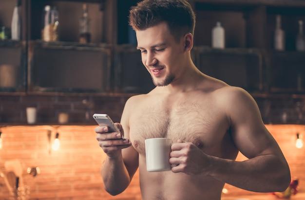 Un mec musclé sexy au torse nu utilise un smartphone.