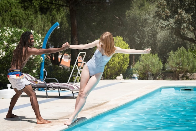Mec noir avec des dreadlocks jouant dans une piscine avec une fille de race blanche.