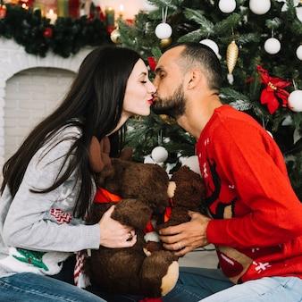 Mec avec ours en peluche embrassant une dame avec duvet moelleux
