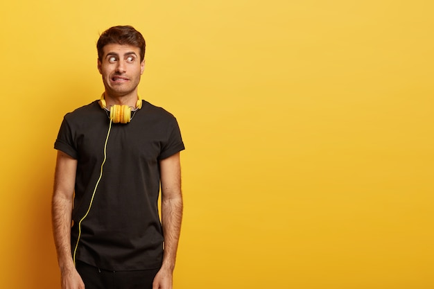 Un mec perplexe aux cheveux noirs, les dents serrées, regarde de côté avec suspicion, porte un t-shirt noir