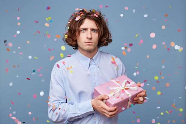 Un mec perplexe et effrayé posant avec une boîte cadeau rose décorative