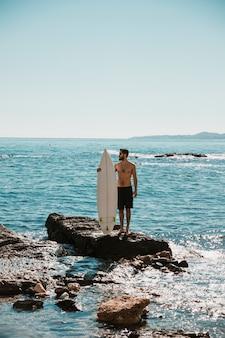 Mec avec planche de surf blanche sur pierre