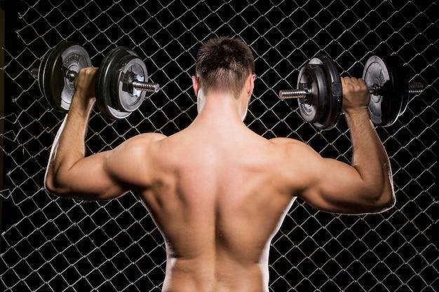 Mec puissant avec un haltères montrant les muscles sur la clôture