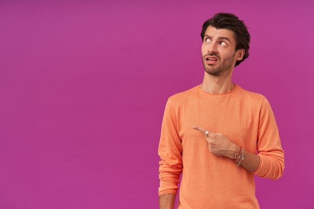 Mec à la recherche confus avec des cheveux et des soies brune. porter un pull orange à manches retroussées