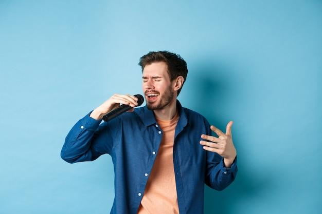 Mec romantique chantant la chanson dans le microphone et le geste, chanteur jouant au karaoké, debout sur fond bleu.
