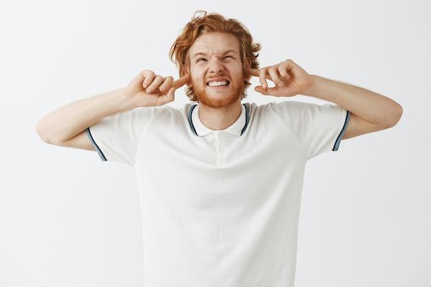 Mec rousse barbu agacé posant contre le mur blanc