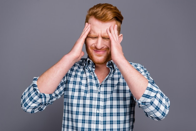 Mec rousse dans une chemise à carreaux bleue posant contre le mur gris