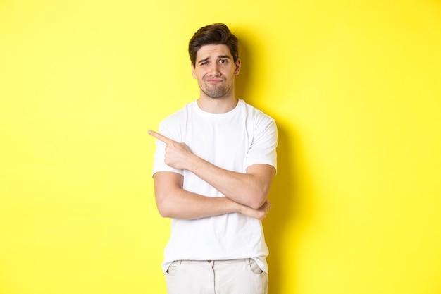 Mec sceptique et réticent en t-shirt blanc, pointant le doigt vers la gauche et souriant sans amusement, montrant une mauvaise publicité, debout sur fond jaune