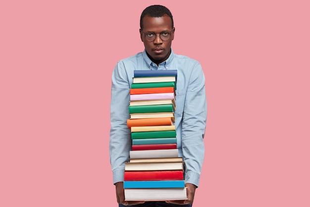 Un mec sérieux à la peau foncée regarde avec une expression insatisfaite, a beaucoup de livres à lire, vêtu de vêtements élégants