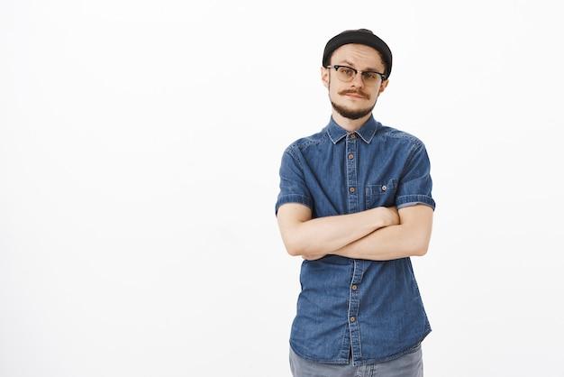 Un mec snob et arrogant désintéressé avec une moustache à lunettes et un bonnet noir tenant les mains croisées sur la poitrine soulevant les sourcils de l'incrédulité et du doute