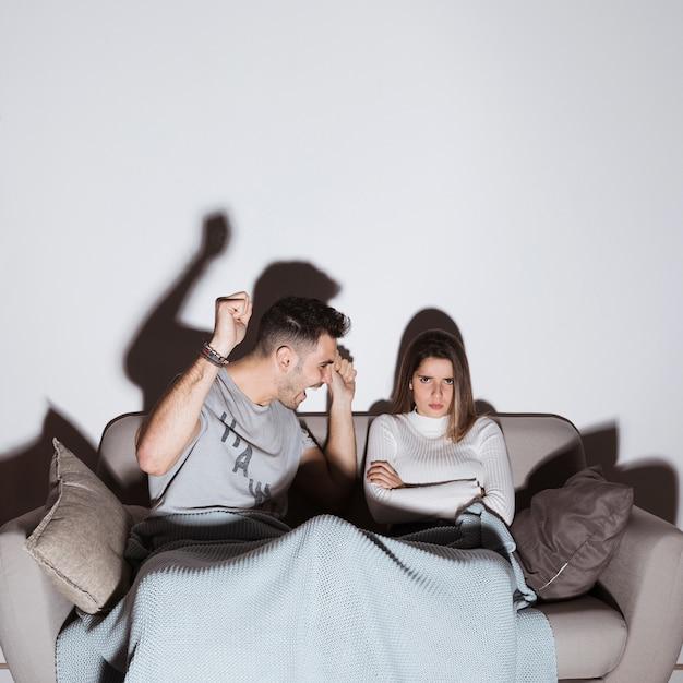 Mec souriant et dame en colère devant la télé sur un canapé