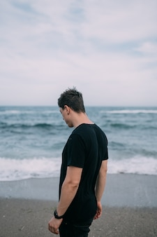 Un mec souriant dans un t-shirt noir se dresse sur le bord de mer de sable. journée d'été, ciel bleu avec nuages blancs, vagues avec mousse blanche.