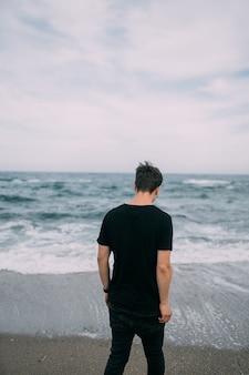 Un mec souriant dans un t-shirt noir se dresse sur le bord de mer de sable.