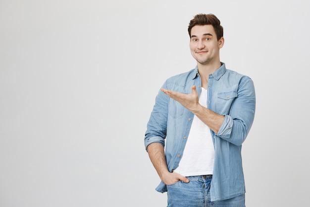 Un mec souriant gai présente la bannière, pointant la main vers la gauche
