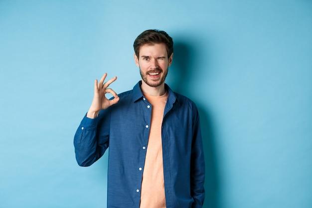 Un mec souriant positif clignant des yeux et montrant un signe correct, louant le bon travail, recommandant une bonne compagnie, debout sur fond bleu.