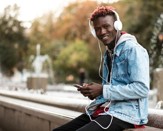 Mec souriant smiley écoutant de la musique