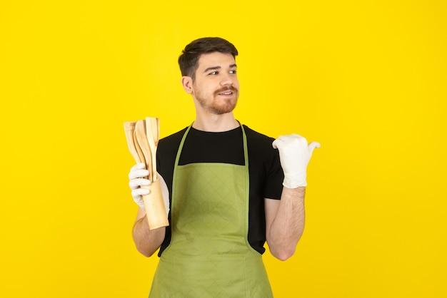 Mec souriant tenant des cuillères de cuisine en bois et regardant loin sur un jaune.