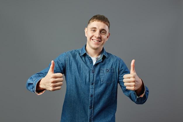 Un mec souriant vêtu d'une chemise en jean garde les deux pouces levés en studio sur fond gris.