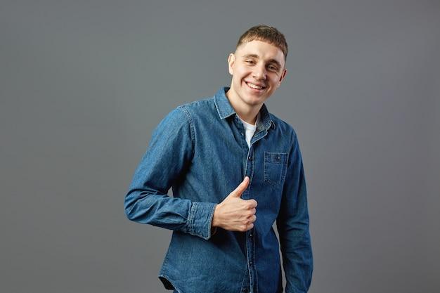 Un mec souriant vêtu d'une chemise en jean garde le pouce levé en studio sur fond gris.