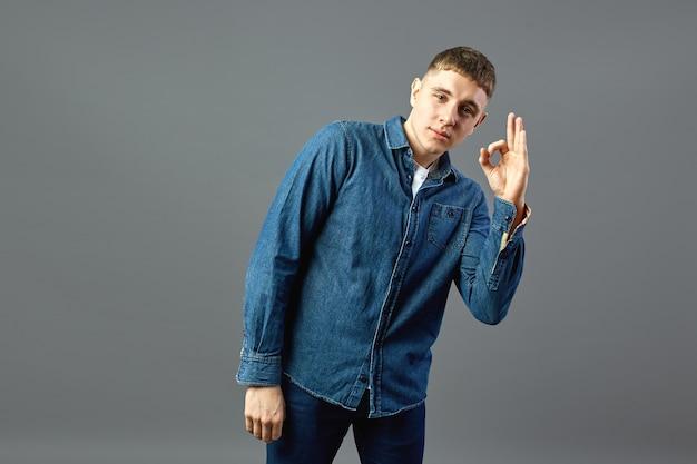 Un mec souriant vêtu d'une chemise en jean montre avec ses doigts des signes ok en studio sur fond gris.
