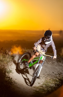 Mec sportif en casque et lunettes à vélo de montagne