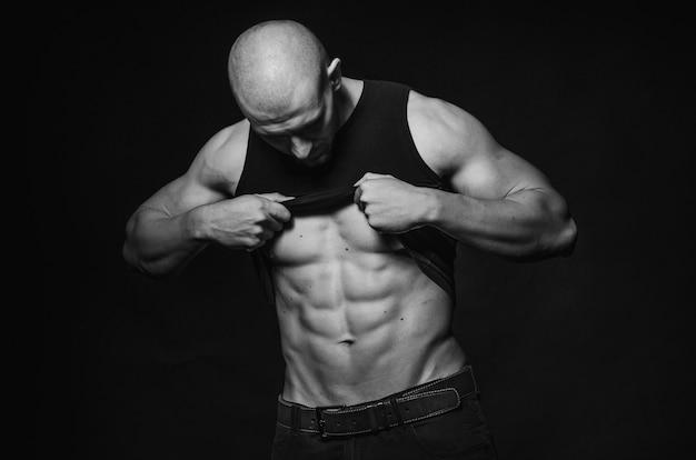 Mec sportif posant en studio sur le fond. sports, beauté, photographie noir et blanc.