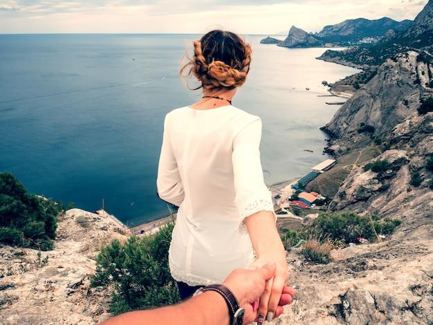 Mec suit une belle fille lui tenant la main dans le voyage touristique au bord de la montagne