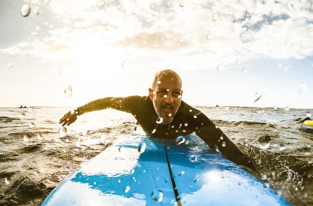 Mec surfeur pagayant avec planche de surf au coucher du soleil à tenerife
