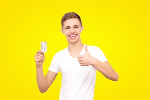 Un mec en t-shirt blanc avec une carte de crédit et le geste d'une classe