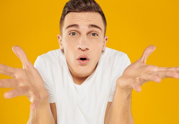 Un mec en t-shirt blanc écarte les bras sur les côtés sur un modèle d'émotions sur fond jaune. photo de haute qualité