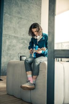 Mec avec tatouage. beau jeune homme étant musicien professionnel et jouant à la maison assis les jambes croisées