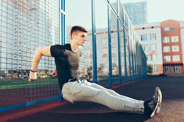 Mec tendu avec un corps musclé à l'entraînement près de la clôture le matin sur le stade. il porte des vêtements de sport, écoutant de la musique avec des écouteurs. il a l'air concentré.