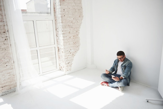 Un mec en tenue décontractée est assis à la maison dans un appartement vide, tenant une carte de crédit et appelant au téléphone. peut-être est-il un nouveau résident et n'a pas encore acheté de meubles.