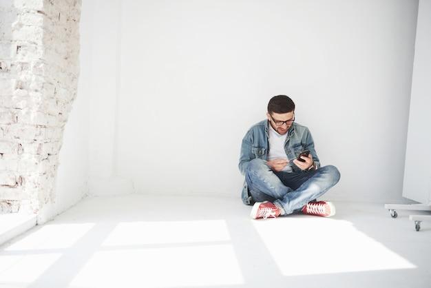 Un mec en tenue décontractée est assis à la maison dans un appartement vide tenant une carte de crédit