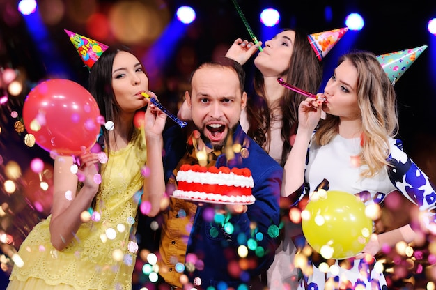 Un mec et trois filles se réjouissent et célèbrent la fête dans la discothèque