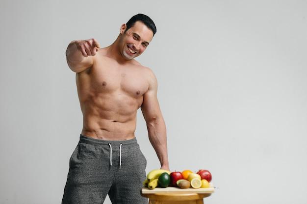 Mec vegan sexy avec un torse nu posant dans le studio à côté de fruits. régime. régime équilibré