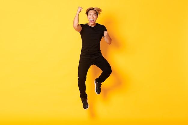 Mec en vêtements noirs sautant et célébrant la victoire