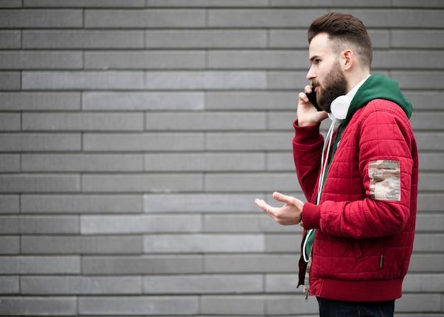 Mec, vue côté, à, écouteurs, parler, téléphone