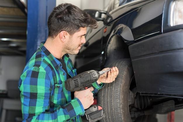 Mecanic vérifiant le système de suspension de voiture, au centre de réparation.